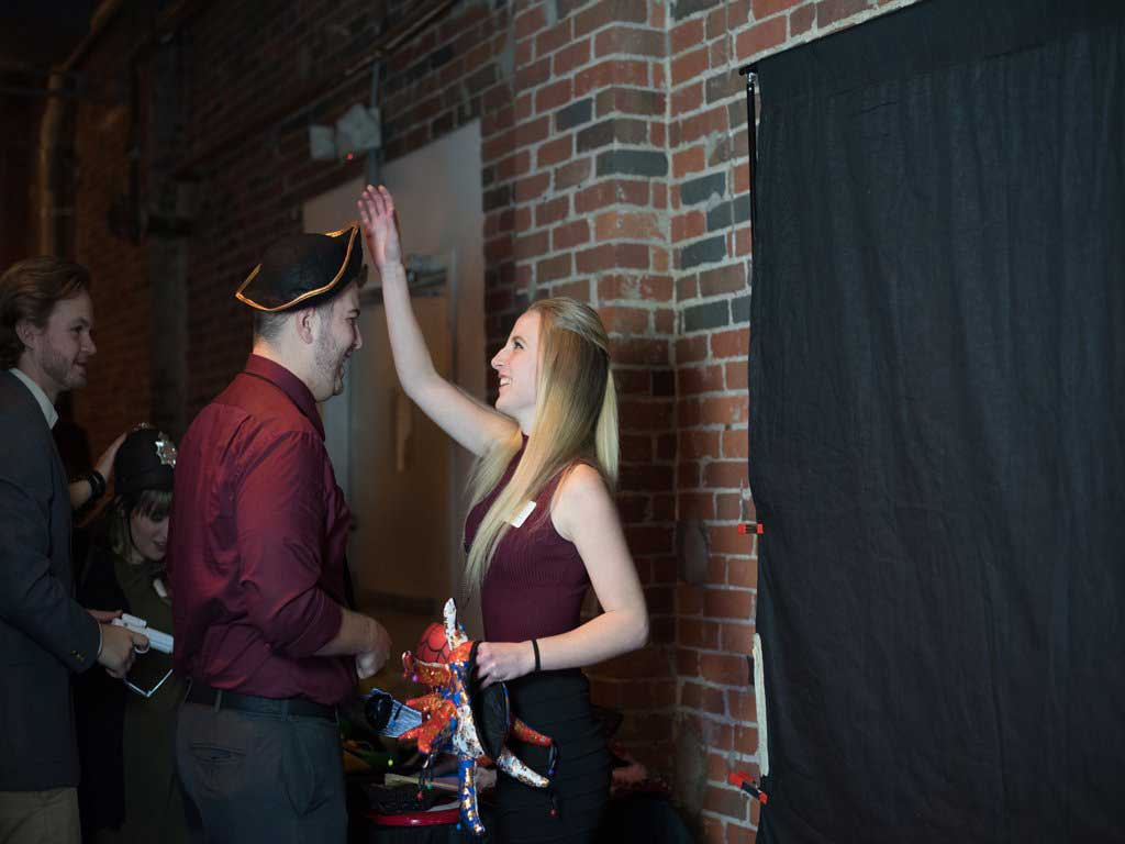 A couple having fun putting on our props for the Fashion Runway Photo Booth.